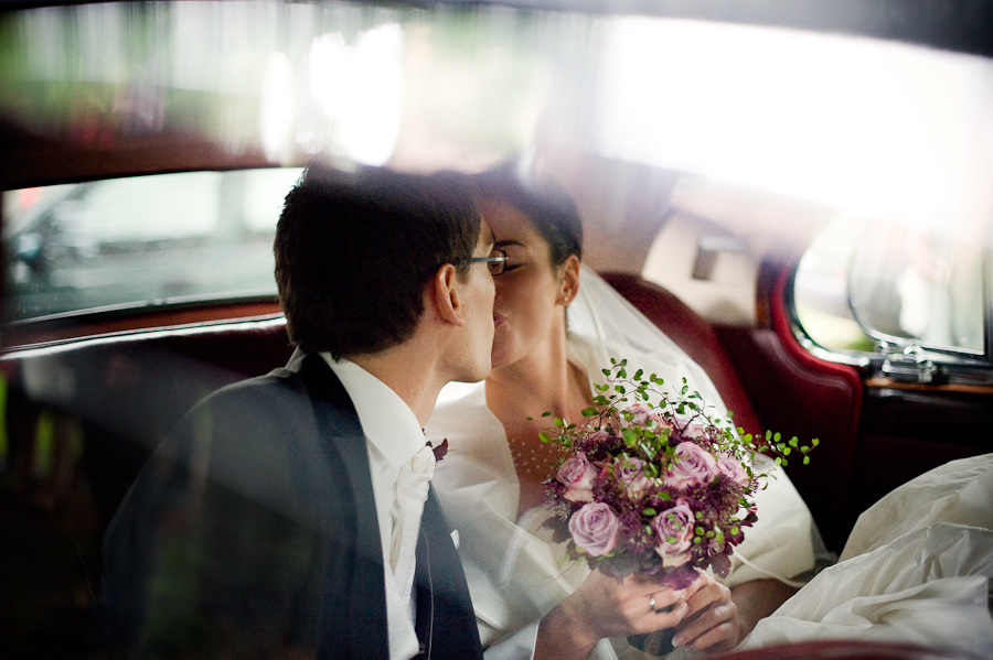 Küssendes Brautpaar im Fond eines Hochzeitsautos.