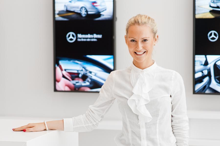 Unternehmensfotografie Bremen - Bild einer jungen, blonden Frau vor Markenlogo