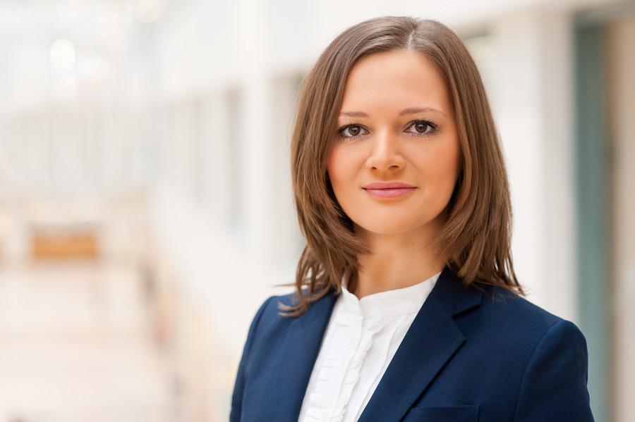 Bewerbungsfoto einer Frau, im Hintergrund der Flughafen Bremen von Innen